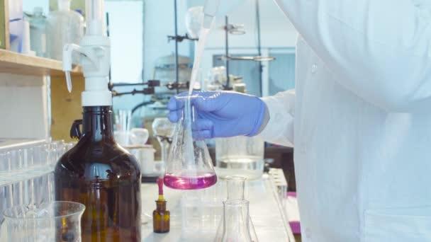Hände eines Wissenschaftlers titrieren Lösung