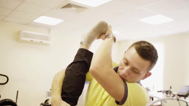 Portrait of doctor helping disabled man at the rehabilitation center