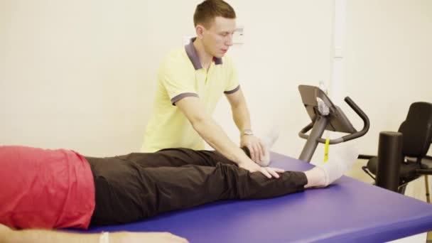 Doctor doing leg exercises for disabled man