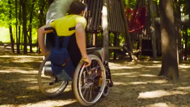 Mladá zakázat muž na invalidním vozíku v parku