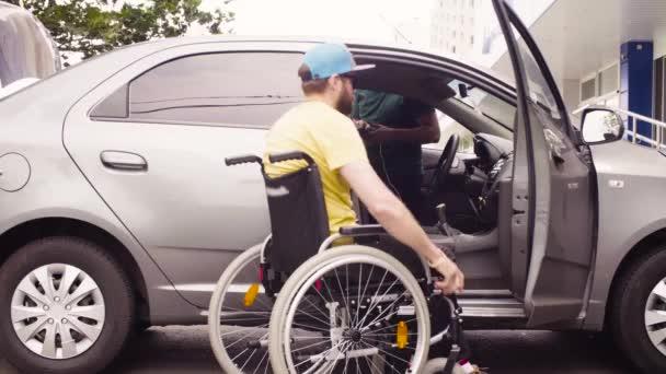 A man in a wheelchair and a woman near the car