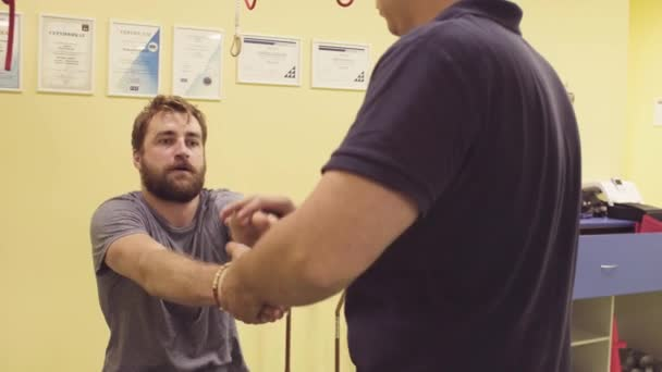 Doctor helping sportsman at the rehabilitation center