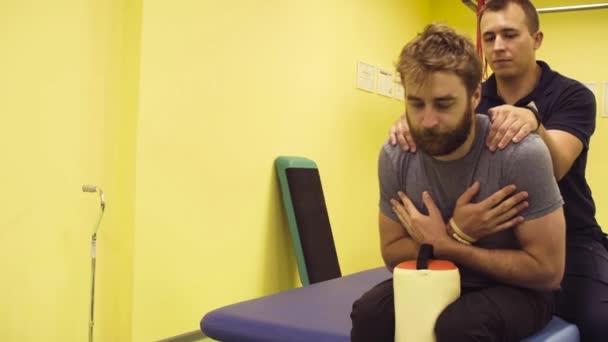 Lékař pomáhá mladý muž v rehabilitačním centru