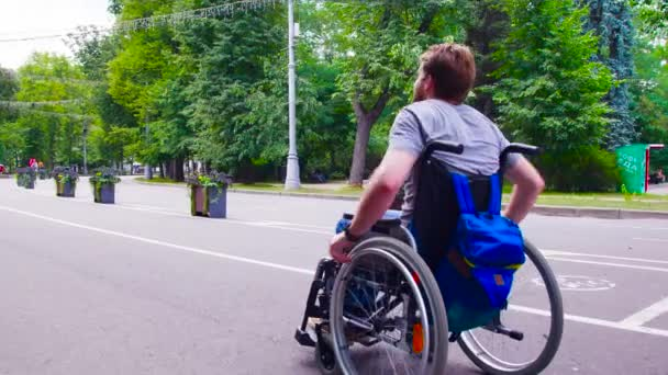 Mladá zakázat muž v parku na vozíku