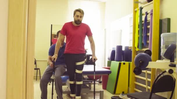 Neplatné v ortéze se snaží chodit s podporou dvou vycházkové hole