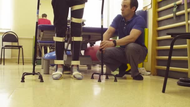 Nohy zakázat člověka v ortéza s podporou dvou chůzi hůl v rehabilitační klinice. Doktor mu pomáhá