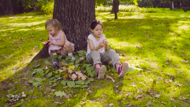 Two girls sitting in the park and eating garnet