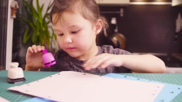 Scrapbooking. Bambina che fa una cartolina. Lei è il taglio fiori da una carta. Creatività dei bambini, artigianato