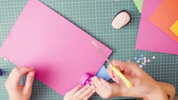 Vista dallalto. Scrapbooking. Mani di bambina taglio fiori di carta colorata. Creatività dei bambini, artigianato