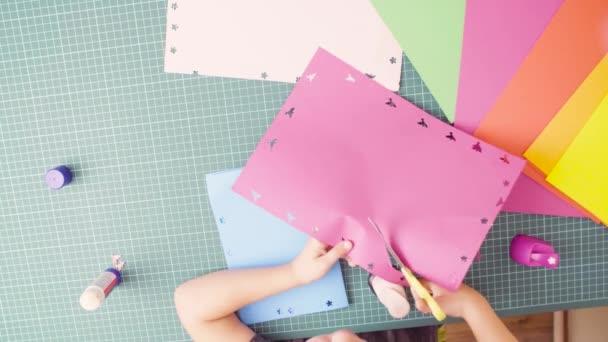 Mani della bambina taglio carta colorata con le forbici