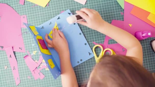 Mani della bambina incollaggio di carta colorata