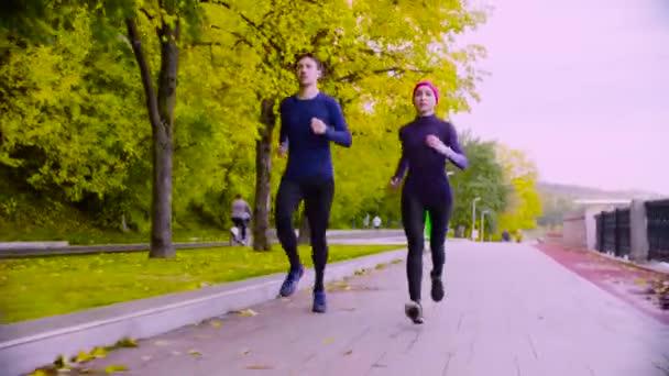 Mladá žena a muž běží v parku. Podzim