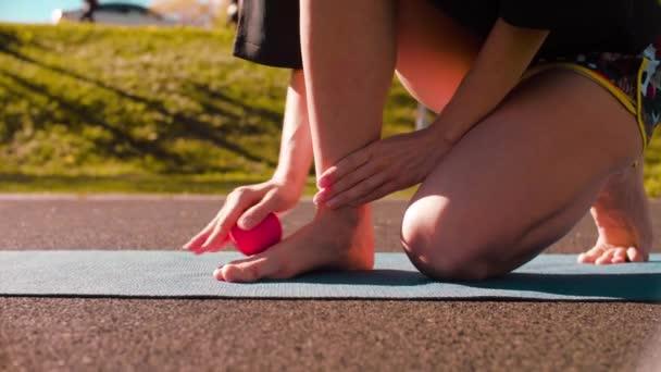 Žena, která dělá masáž nohou s míčem