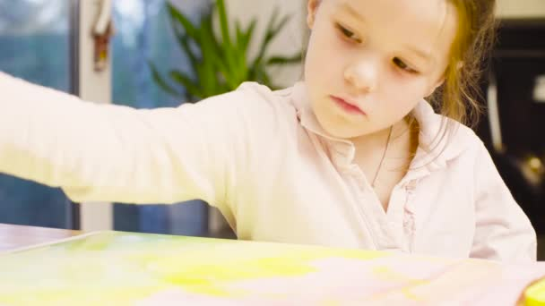 Young artist painting on paper with watercolors