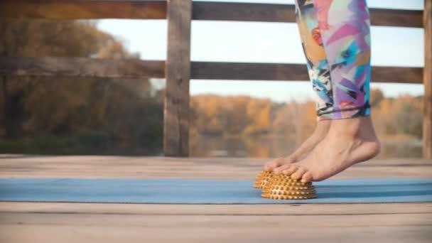 Žena, která dělá masáž nohou s polokoule polštář