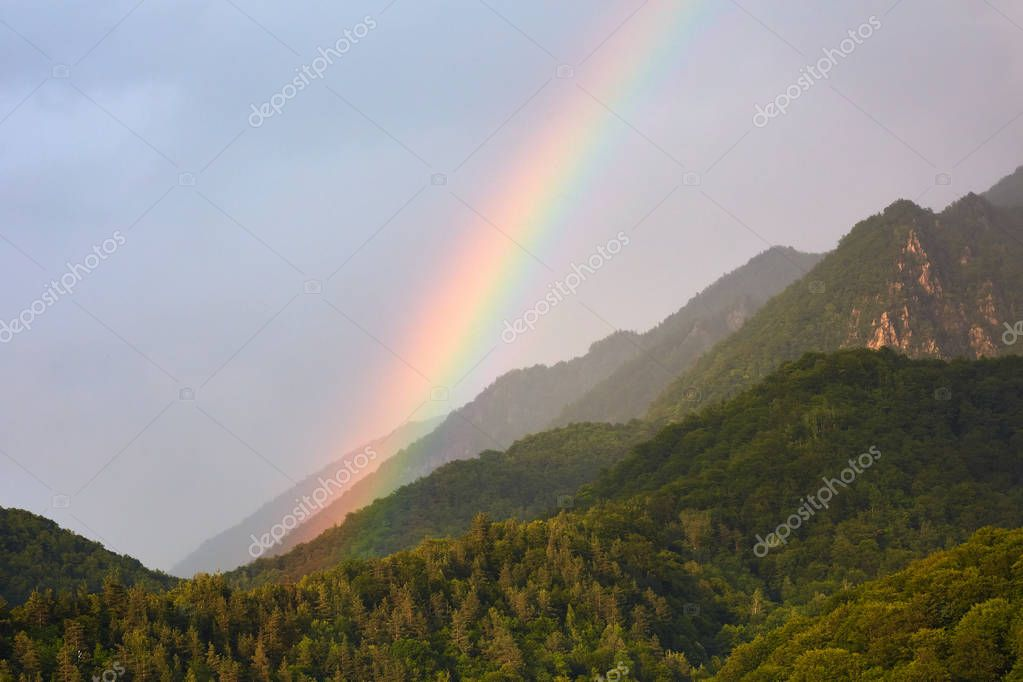 beautiful rainbow in cloudy sky over mountains