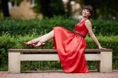 Atraktivní mladá dívka v červených šatech sedí na lavičce v parku