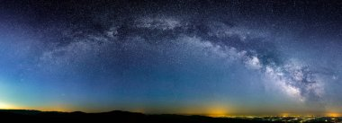 Panoramic shot of Milky Way's galactic arc over city lights