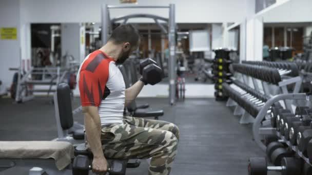 Člověk dělá biceps curl s činkami v posilovně