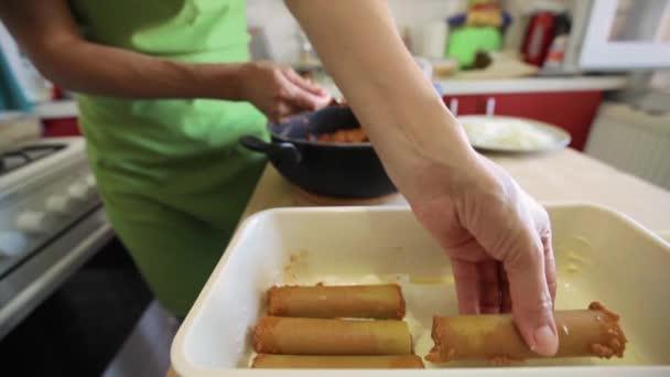 Detailní záběr na rukou osoby plnící canneloni v interiéru kuchyně