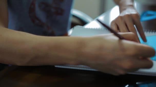 Nahaufnahme eines männlichen Schülers, der Hausaufgaben in ein Textbuch schreibt