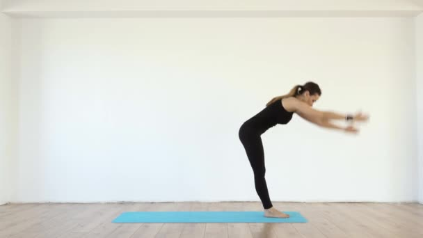 Young female yoga teacher in studio taking various poses on white wall background