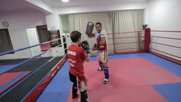 Young kickboxing fighter hitting pads with his coach in gym
