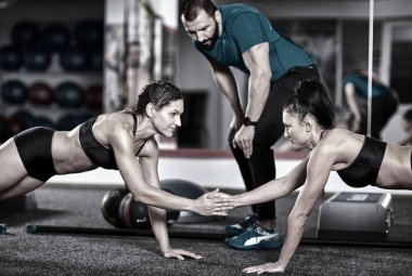 Fitness trainer and girls doing crossfit workout in the gym