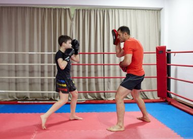 Young kickboxing fighter hitting mitts with his coach