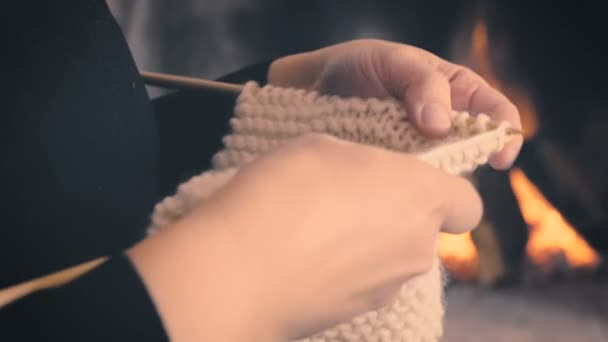Close up of woman hands knitting by the fireplace in warm winter blur background. Girl doing relaxing knit activity with wool indoor at home. Camera pan from left to right 4k footage.
