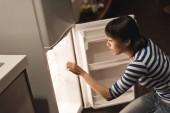 Ázsiai nő nyitott hűtőszekrény otthon