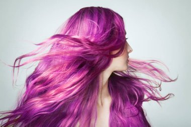 Portrait of Young Beautiful Woman with Long Flowing Hair. Model with Perfect Healthy Dyed Hair. Pink Hairstyles