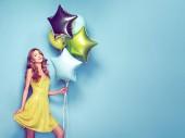 Gyönyörű fiatal nő, színes buborékok a kék háttér. Születésnapja, és fél. Lány a zöld ruhát a fesztiválon