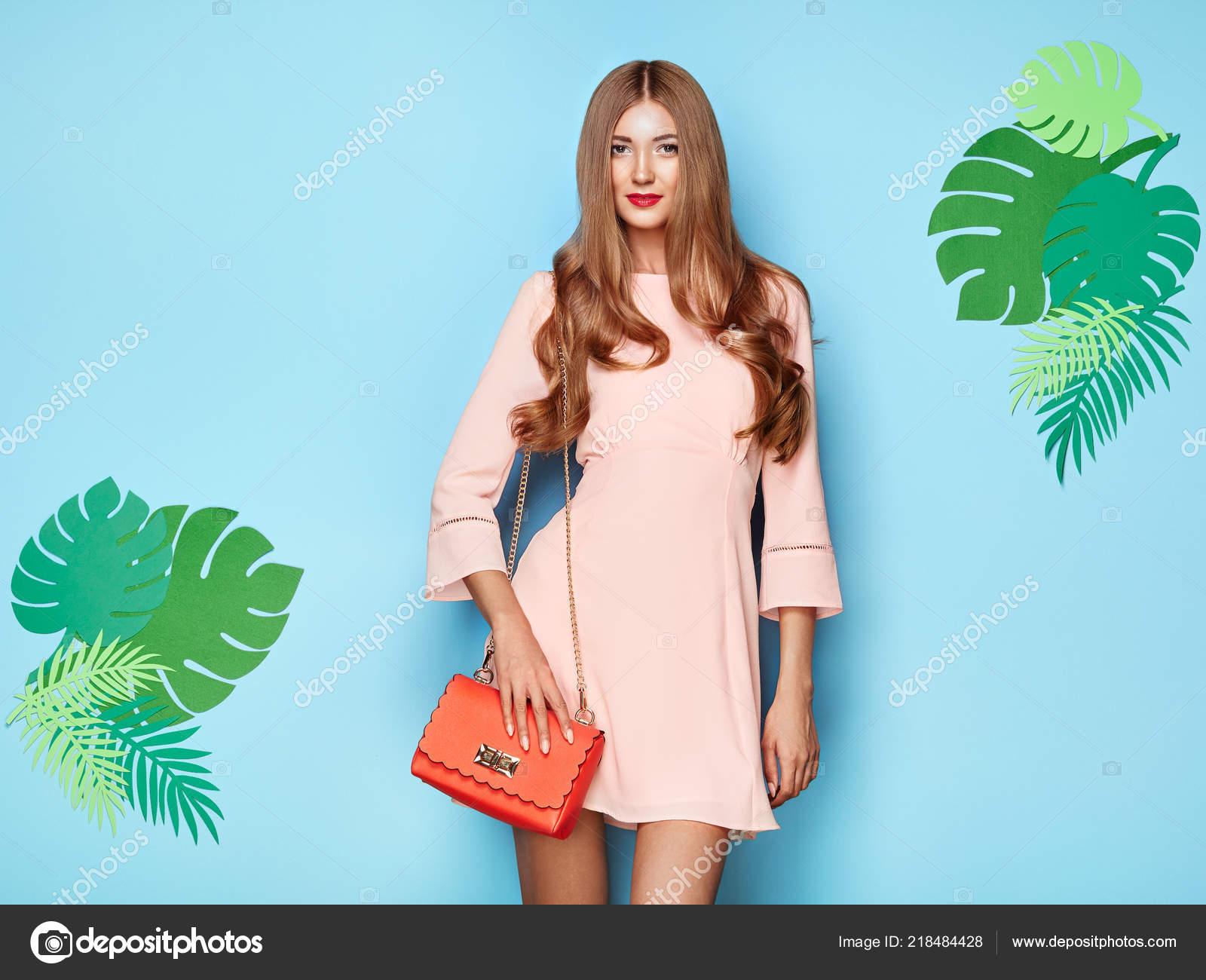 346e837b1308 Ritratto di giovane moda donna in abito rosa. Signora in abito estivo  elegante. Ragazza in posa su uno sfondo blu. Acconciatura alla moda.