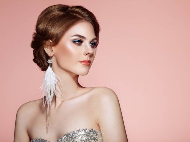 Beautiful Woman with Large Earrings Tassels Jewelry White Color. Perfect Makeup and Elegant Hairstyle. Blue Make-up Arrows