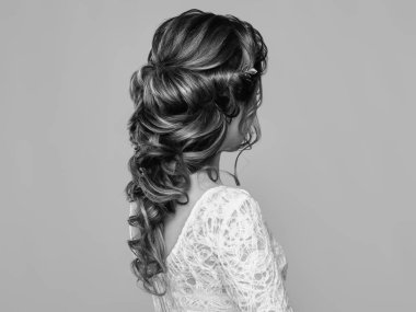 Brunette Woman with Long and shiny Curly Hair. Beautiful Model Lady with Curly Hairstyle. Care and Beauty Hair products. Care and Beauty of Hair