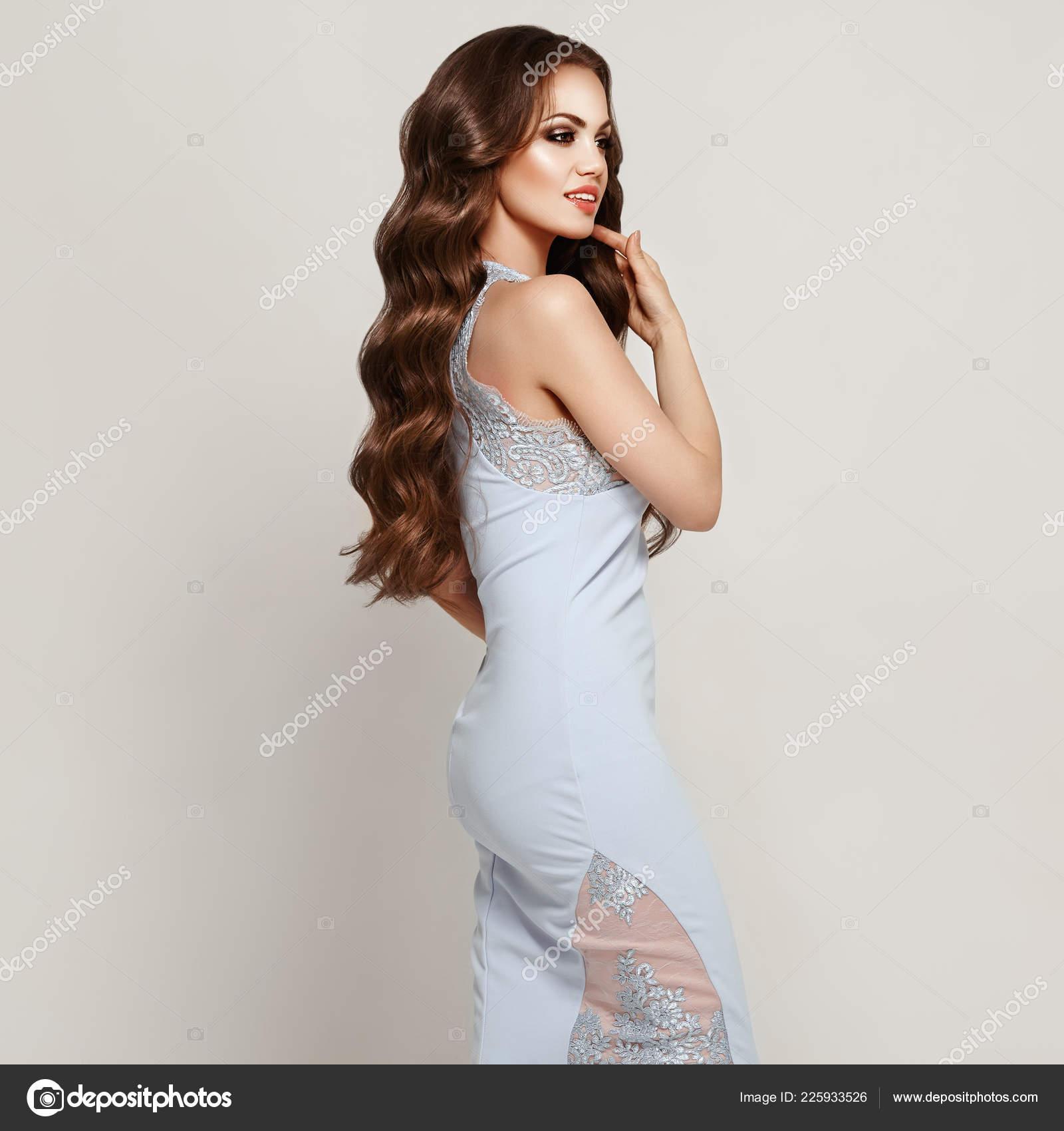 a9e19a571a1c0 Belle femme en robe de soirée élégante blanc. Jeune fille brune aux cheveux  bouclés longs saine et brillante. Soins et beauté. Beau modèle femme avec  une ...