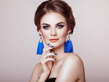 Beautiful Woman with Large Earrings Tassels jewelry Blue color. Perfect Makeup and Elegant Hairstyle. Blue Make-up Arrows