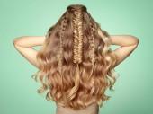 Szőke lány hosszú, fényes göndör haj. Gyönyörű modell nő göndör frizura. Ellátás és a kozmetikai hajápolási termékek. A fonott hajú hölgy