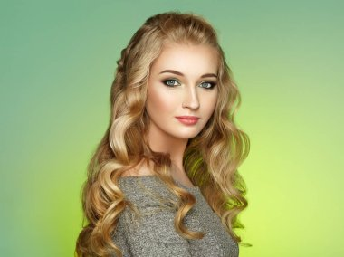 Blonde Girl with Long and Shiny Curly Hair. Beautiful Model Woman with Curly Hairstyle. Care and Beauty Hair Products. Lady with braided hair
