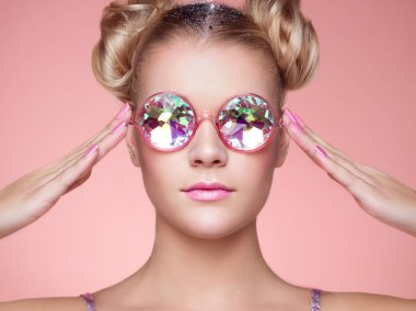 Portrait of Beautiful young Woman with Colored Glasses. Beauty Fashion. Perfect Make-up. Pink Nails Manicured. Colorful Decoration. Hair Curled into a Bun