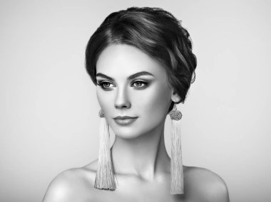 Beautiful Woman with Large Earrings Tassels jewelry. Perfect Makeup and Elegant Hairstyle. Fashion Make-up Arrows. Black and White Photo