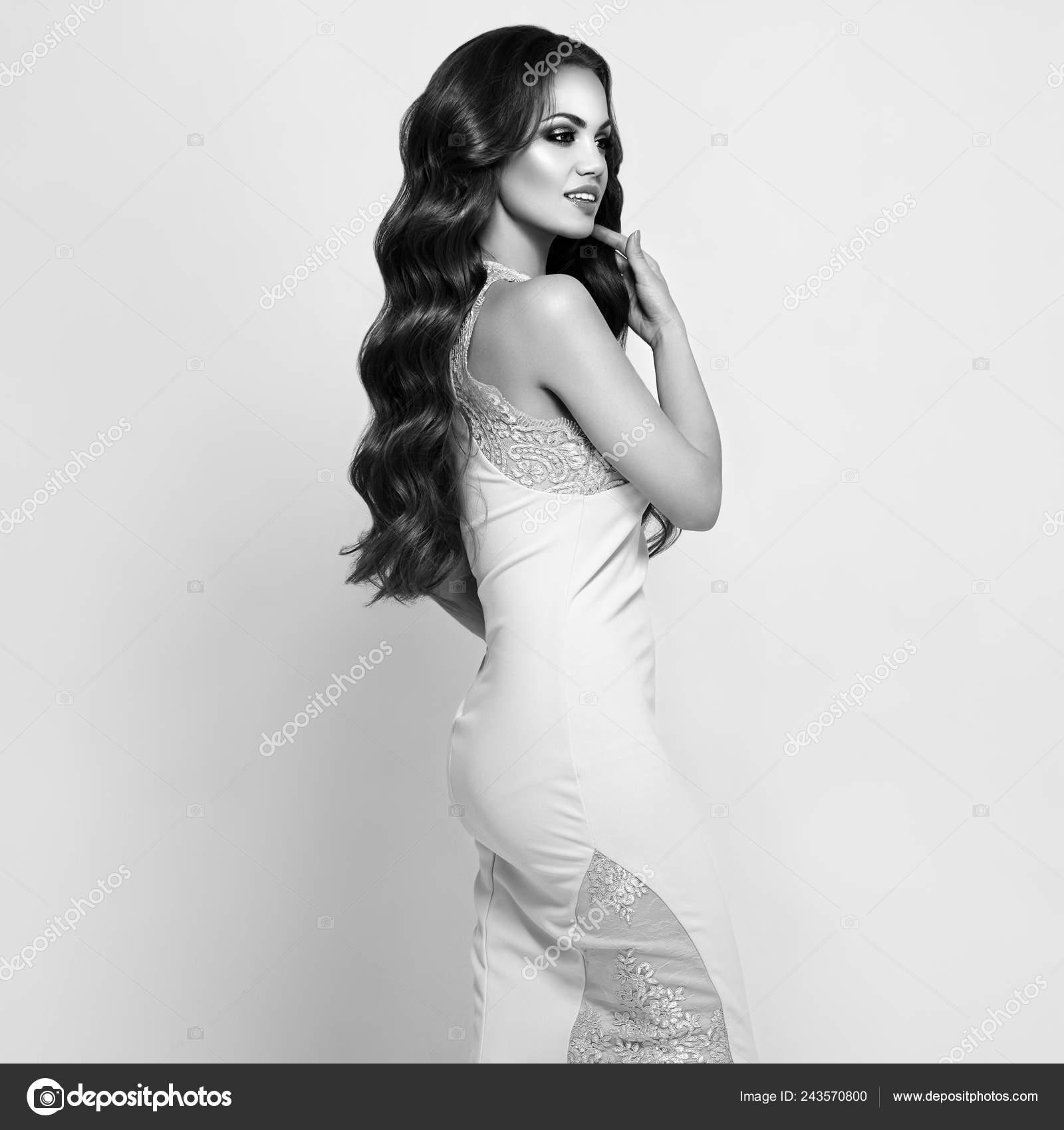 5b561ec49e Hermosa mujer en vestido de noche blanco elegante. Chica morena con el pelo  rizado largo brillante y saludable. Cuidado y belleza. Hermosa modelo mujer  con ...