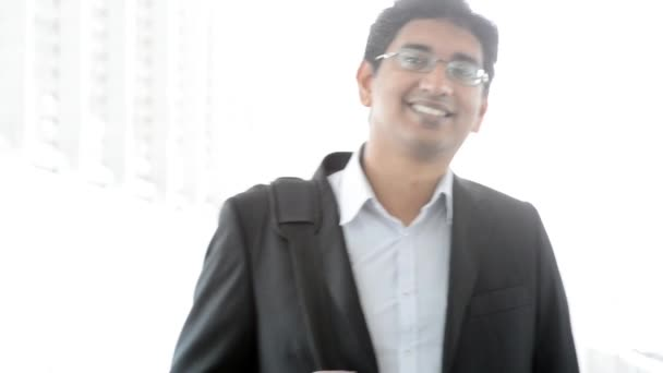 Portrait of a good looking smiling Indian businessman standing at modern building, with natural light.