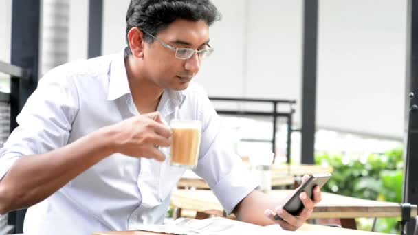 Asian Indian businessman using smartphone at cafeteria