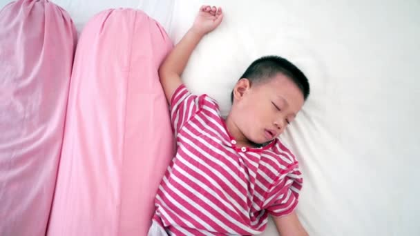 Pět let staré asijské boy spící na posteli, video záběry.
