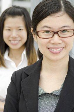 Asian business team, two businesswomen, focus foreground.