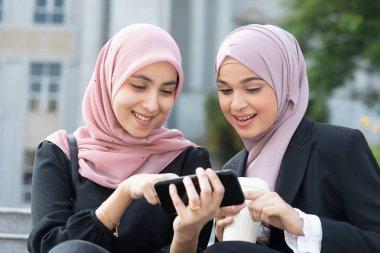 Muslim women using smart phone, sharing and laughing. stock vector
