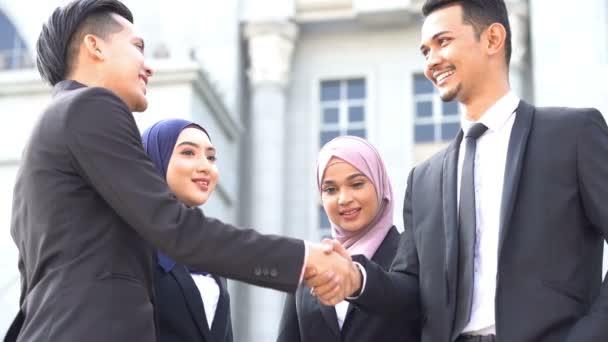 Podnikatelé, kteří se třesou, stojí před budovou, multirasové obchodní koncepce.