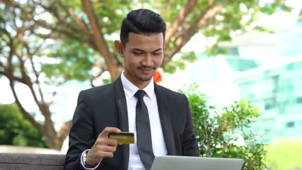 Happy Asian business man cheering, hand holding credit card sitting with laptop outdoor.